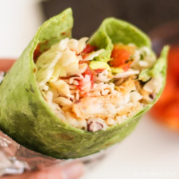 You are going to LOVE these quick and easy fish burritos! Tortillas are stuffed with beans and rice, crispy fish sticks, and all your favorite toppings. It's a family favorite recipe!