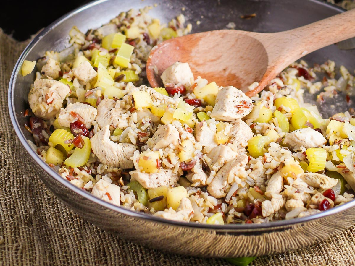 This 30-minute skillet dinner is loaded with dried cranberries, fresh apples, celery, and chicken simmered together with instant brown rice. #cranberry #apple #chicken #rice