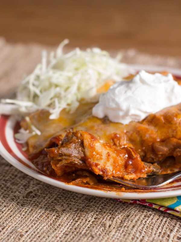 These delicious enchiladas are made easy with 2-ingredient slow cooker shredded beef!