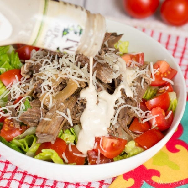 Slow cooker beef loaded with caesar flavor is served on a bed of healthy greens. Super easy, versatile weeknight dinner!