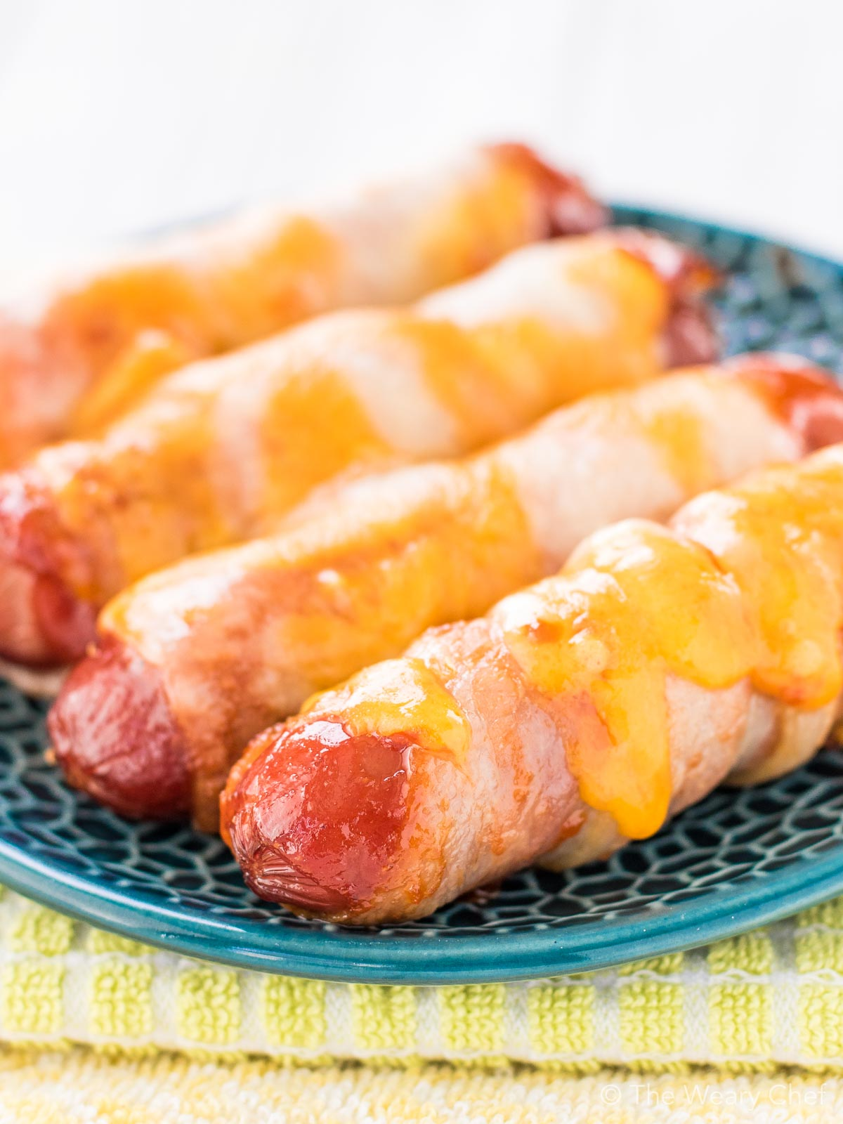 These cheesy BBQ Bacon Wrapped Hot Dogs are fun and easy to make. Perfect for the oven or grill. Serve them on buns or on their own for a lower carb treat!