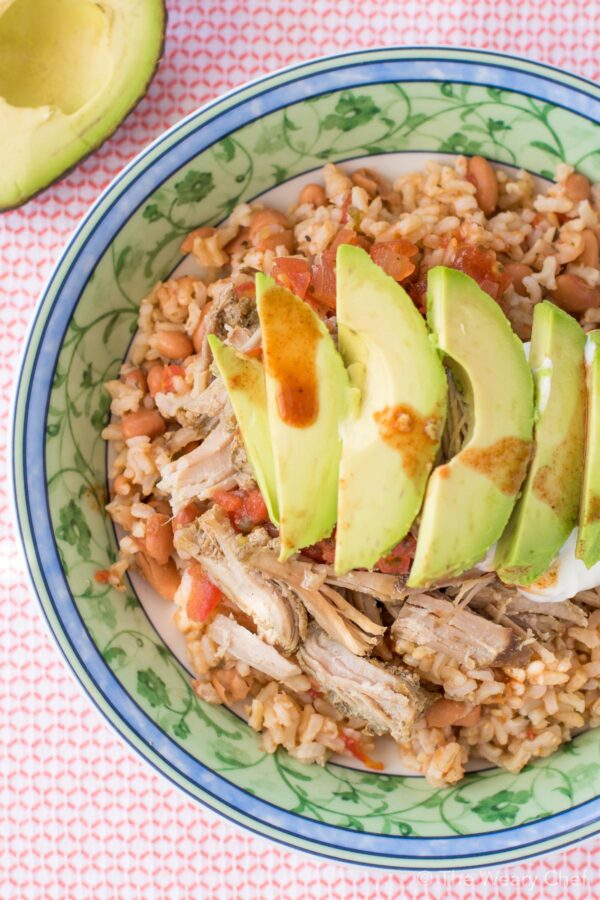 This very easy Mexican Pinto Beans and Rice topped with tender pork carnitas is delicious dinner the whole family will love! Prepare the pork in the slow cooker, and make the beans and rice in one pot in 15 minutes!