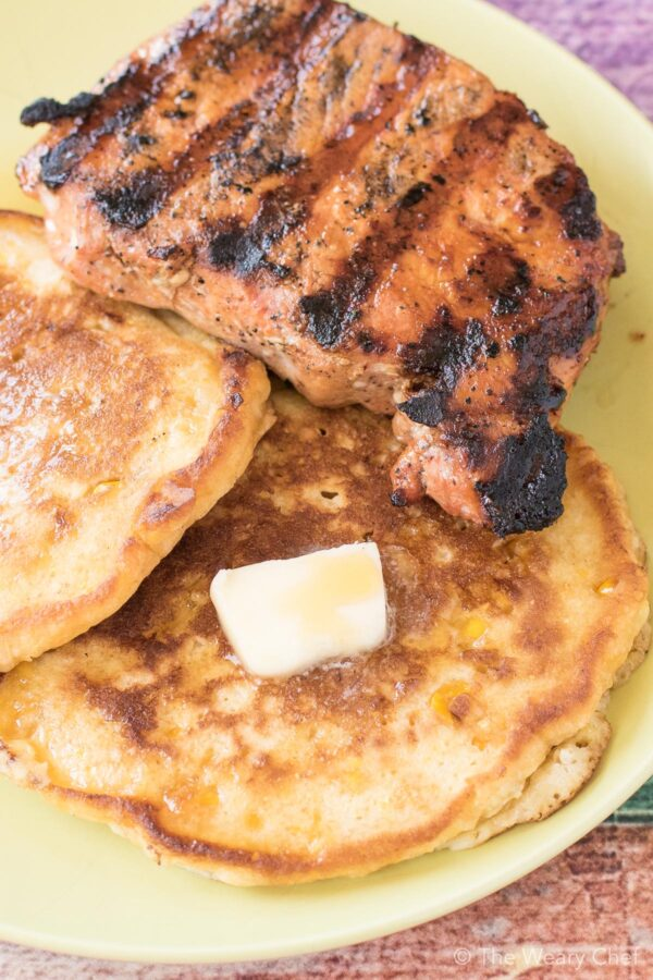 Easy Cream Corn Pancakes paired with freshly grilled pork chops a delicious breakfast or dinner thats ready in 30 minutes!