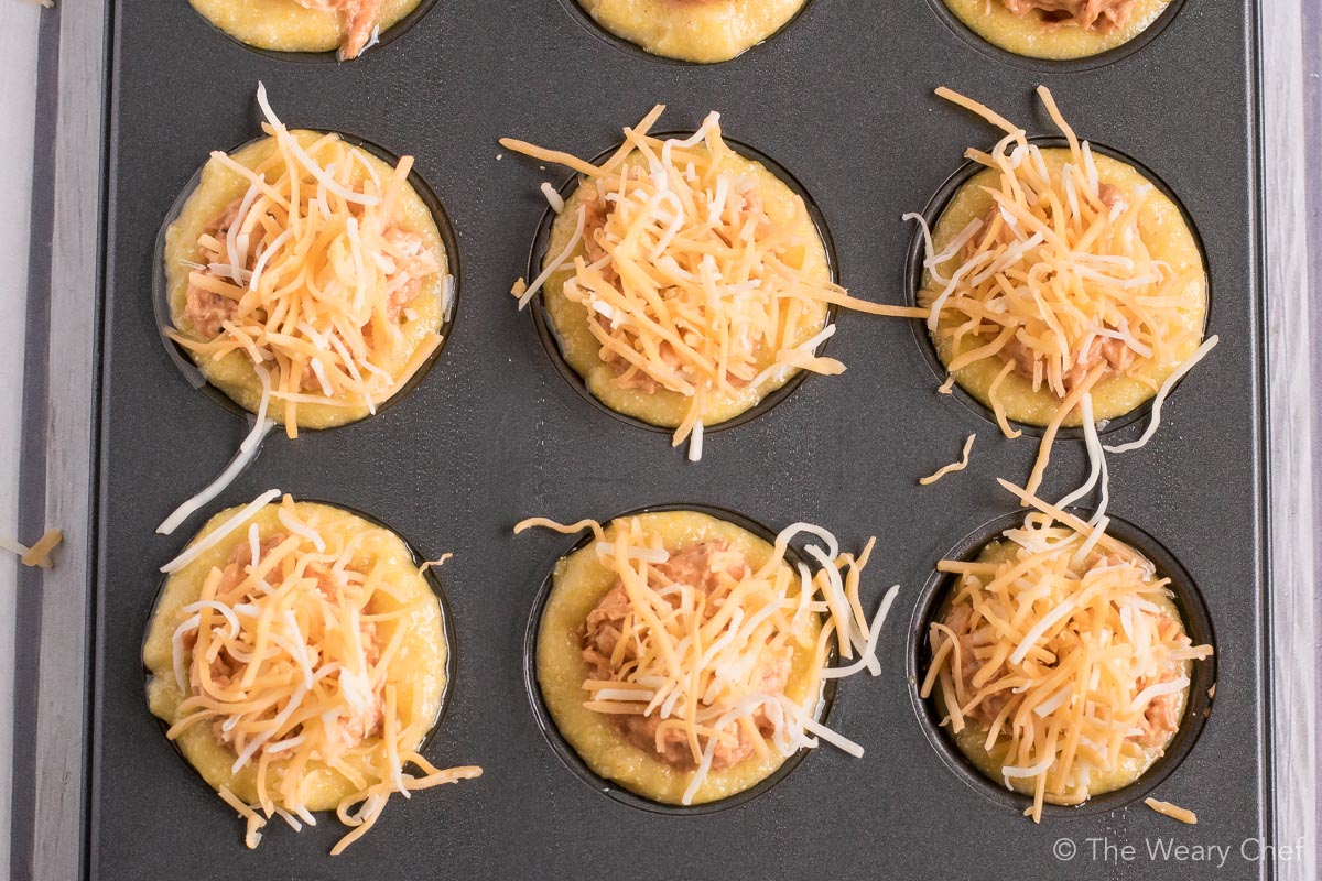 Mini cornbread muffins are stuffed with a creamy BBQ chicken mixture and topped with shredded cheese. Perfect easy recipe for tailgating, parties, and potlucks! #bbq #chicken #recipe