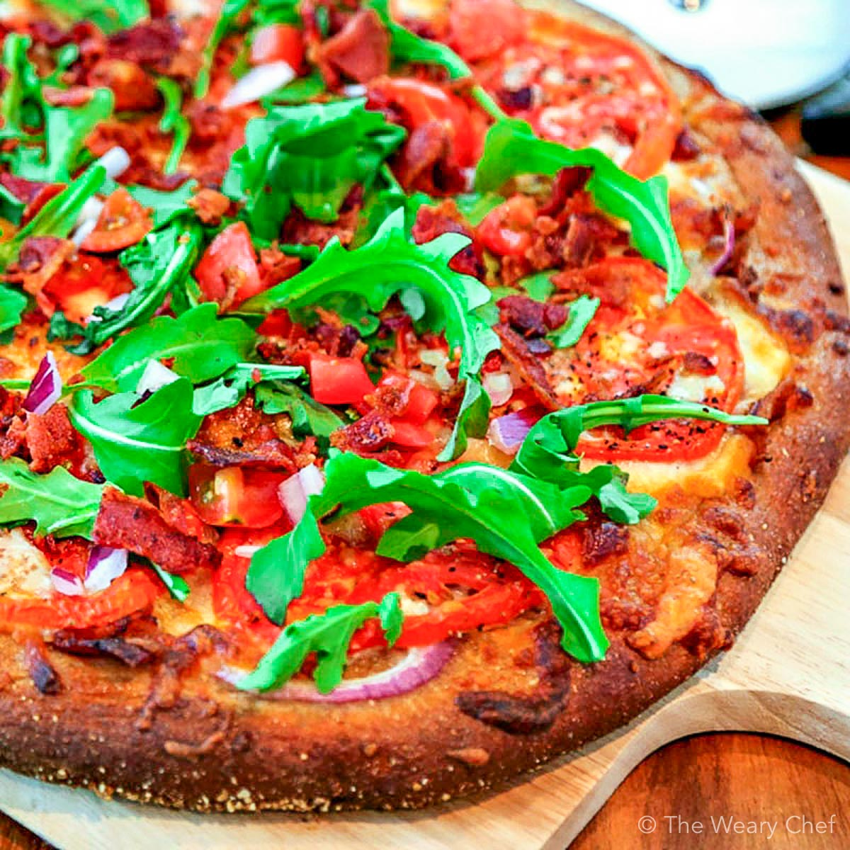 Bite into this BLT pizza loaded with a bacon, red onion, fresh tomatoes, arugula, cheeses, and a garlic-mayo sauce. It's your favorite sandwich turned into a chewy pizza! #blt #pizza #bacon