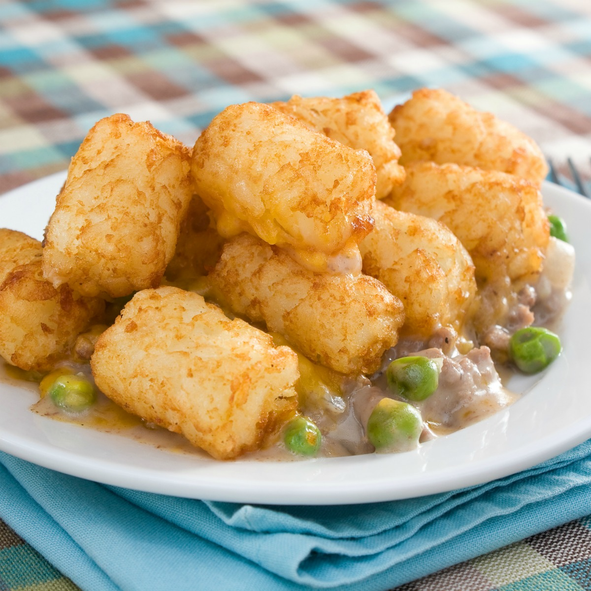 This easy Tater Tot Hot Dish is a perfect family dinner or potluck favorite. A hearty filling is topped with crispy tater tots for a truly comforting meal. #hotdish #casserole #tatertots