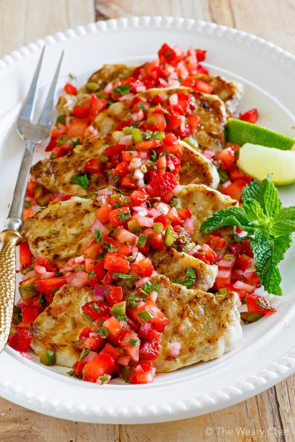 Marinated and grilled pork loin chops are topped with fresh strawberry salsa bursting with mint and jalapeno flavors. This grilling recipe is sure to be the start of any cookout! #grilling #pork #strawberry #salsa #smithfield #sponsored #SmithfieldGetGrilling #RealFlavorRealFast