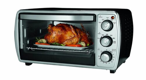 oster toaster oven in stainless steel with perfectly roasted golden brown chicken