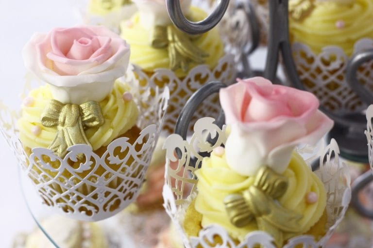 rose-topped cupcakes in lacy cups