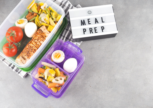 board with meal prep inscriptions near  food in containers