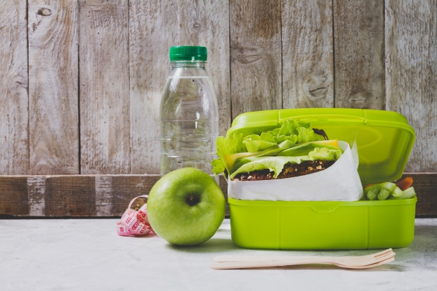 bottle of water , apple and lunchbox