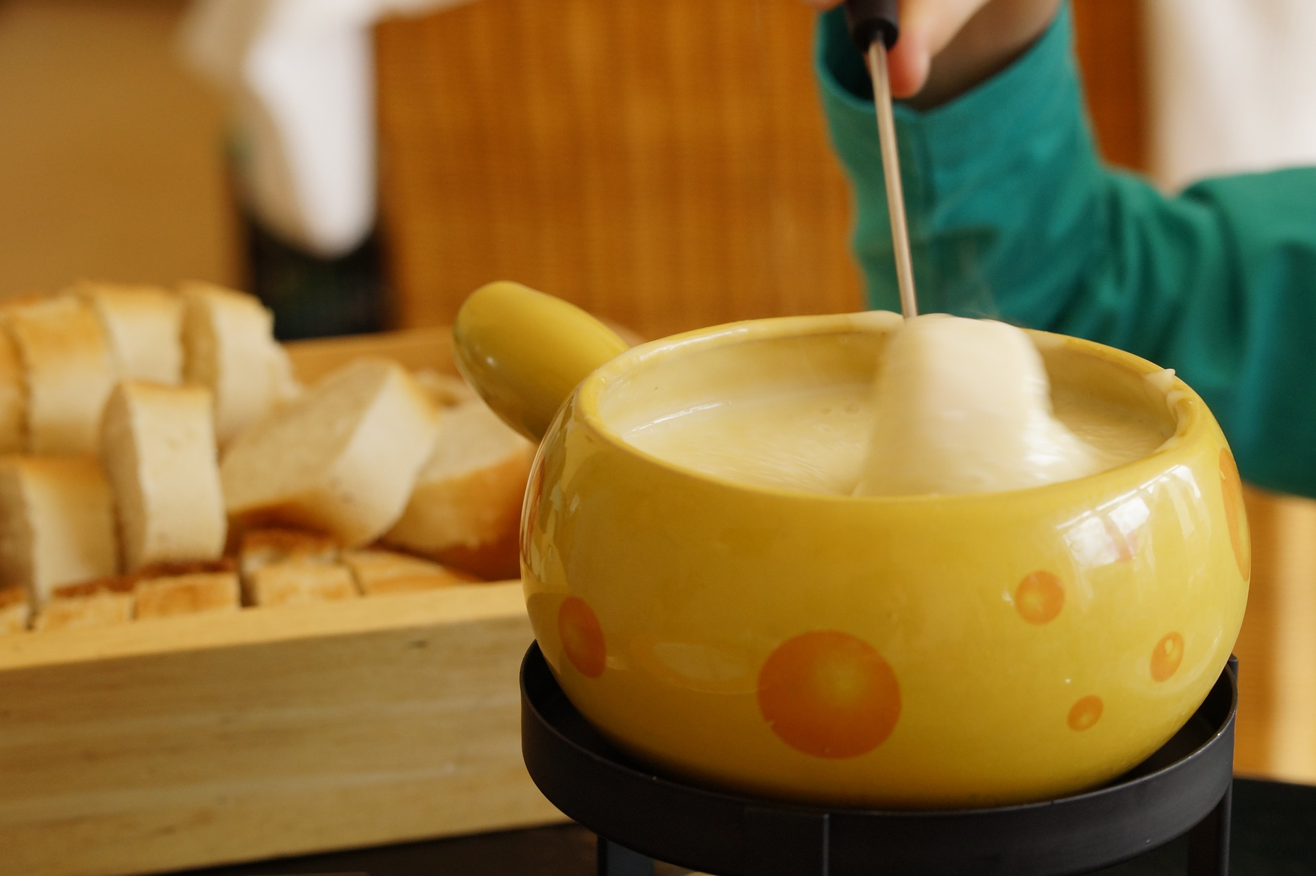 Person is mixing the Swiss cheese fondue in a pot