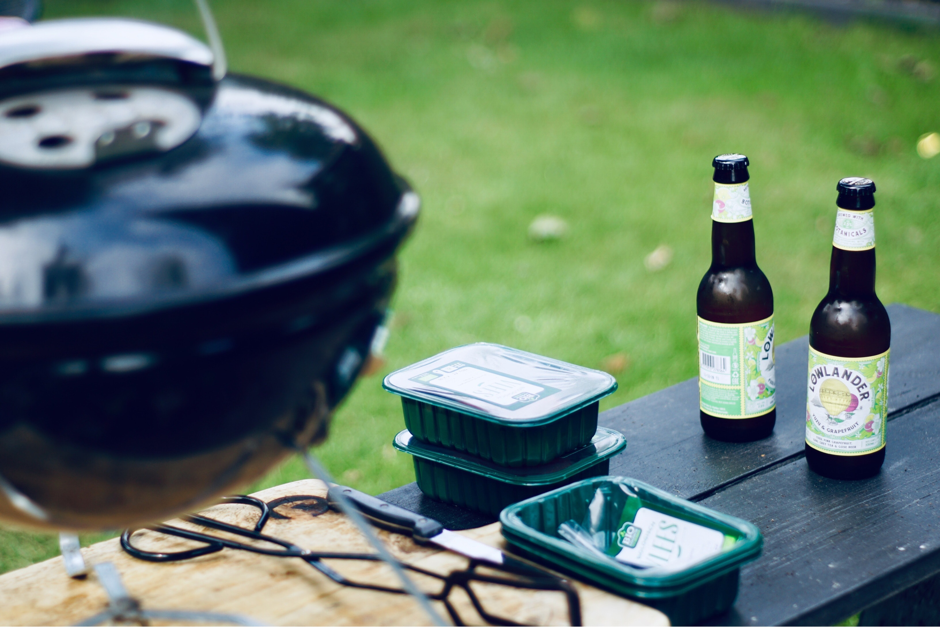 two bottles of beer next to the grill set
