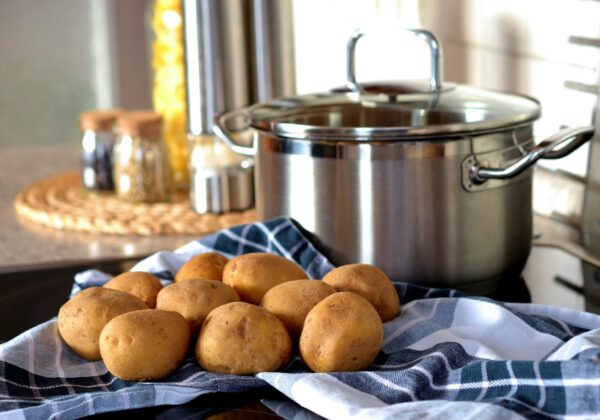 potatoes on a blue towel in front of a large pot
