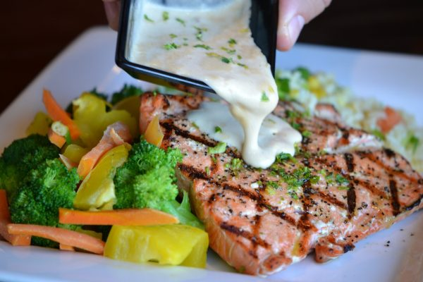 A plate of salmon and vegetables with a white sauce being ooured ofer it