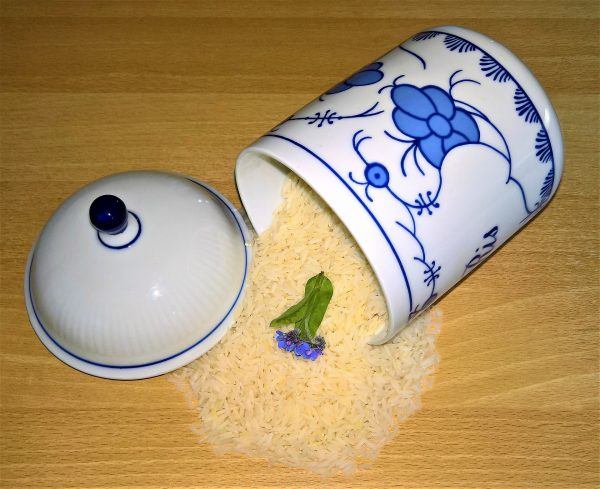 Dry jasmine rice spilling out of a ceramic container